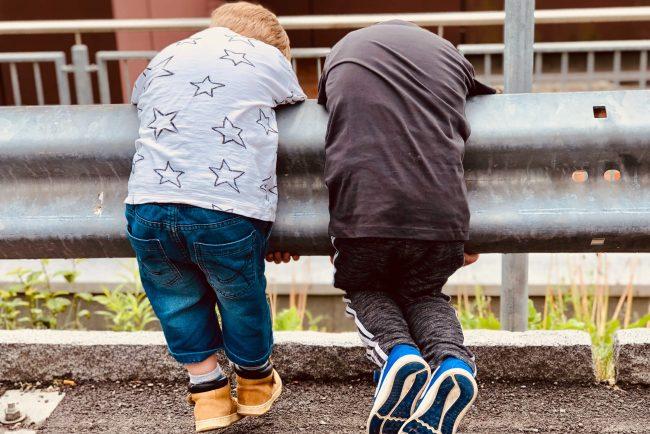 Zwei Kinder lehnen sich synchron über eine Absperrung