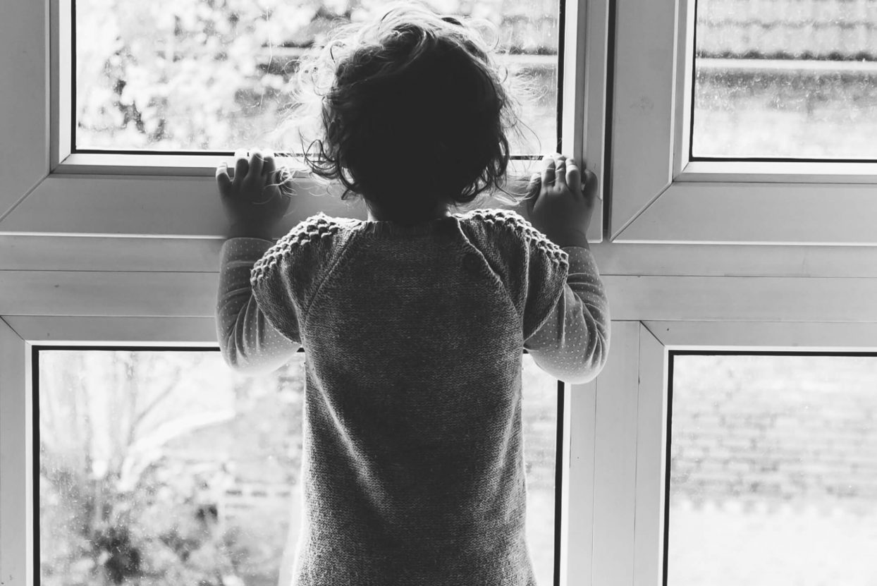 Kind stehen vor dem Fenster