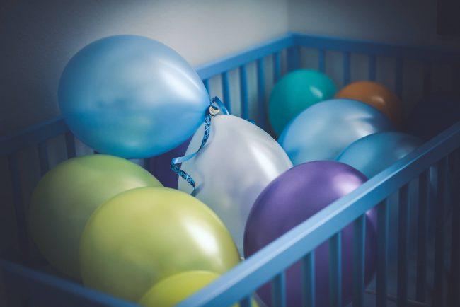 Ein Babybett gefüllt mit Luftballons